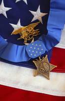 The Medal of Honor rests on a flag beside a SEAL t