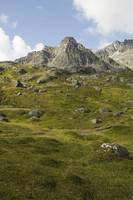 High rugged mountain peaks and green tundra hillsi
