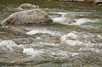 River water flowing downstream around rocks