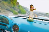 Plastic Hula Doll On The Dashboard Of A Turquoise
