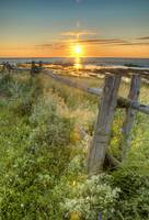 Sunset Over Water With Fence Along The Shoreline