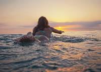 A Woman Laying On A Surfboard Watching The Sunset,