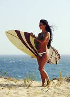 Woman Standing On The Beach With A Surfboard