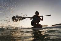 Woman Paddling While On Her Knees On Surf Board, T