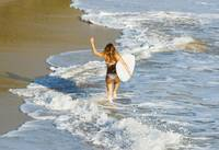 Woman running along beach with surfboard, Tarifa,