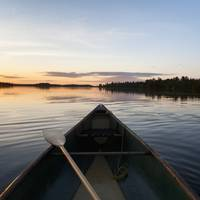 A Boat And Paddle On A Tranquil Lake At Sunset, On