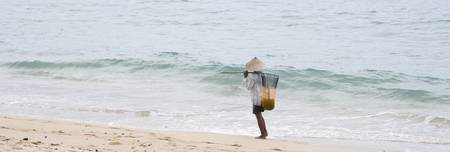 Person Walking On The Beach With A Fishing Net Ba
