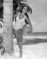 Vintage bathing suit girl leaning against palm tre
