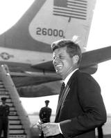 John F. Kennedy smiles as he boards plane