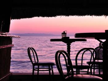 Silhouette of bar chairs and tables in the tropical bar with sea in background at sunset. Podgora, Croatia
