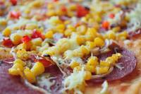 Detail of delicious pizza with corn and salami