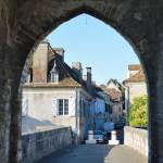 French town through the ancient stone arch Prints & Posters