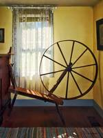 Large Spinning Wheel Near Lace Curtain