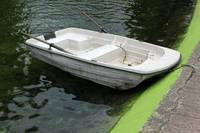 Small Boat Next to a Concrete Pier