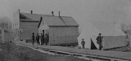 Wood house and Civil War tent in early Crookston
