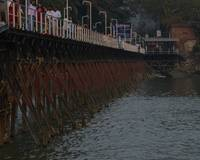 People Walking on Small Bridge on River Ganga