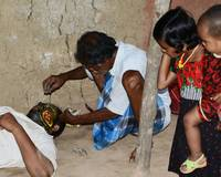 A Man Busy in Face Painting and Children Watching