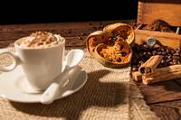 Close-up of coffee cup, dried orange fruit and cin