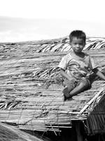 Cambodian boy on thatched roof
