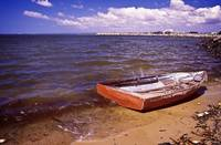 wrecked row boat blur water sky waves cloud