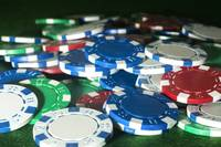 Poker chips thrown baize coloured card table