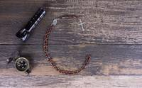 Flashlight, Compass and Rosary on Dark Wood