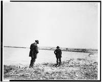 Two men foraging along shoreline, Chicago, Illinoi