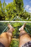 Man laying in hammock on a summer day