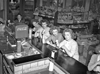 A group of young women eat at the counter of drugs
