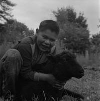 Boy hugging black sheep used for Cowichan sweaters