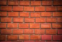 Red brick wall texture with dark vignette