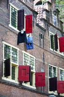 Clothes hanging from a window in Kattengat, Amster