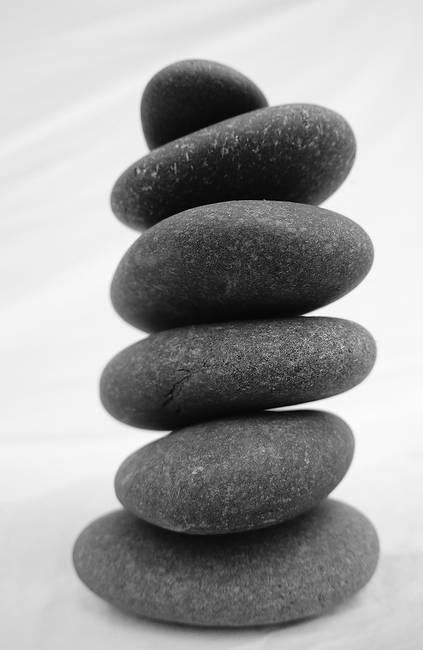 Stacked river rocks on white background