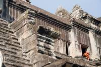 Monk exiting through a window of Angkor Wat, Cambo
