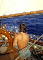 At the helm under sail with blue seas