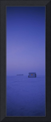Ice fishing shack on a frozen lake