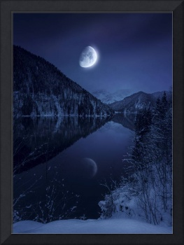 Moon rising over tranquil lake in misty mountains