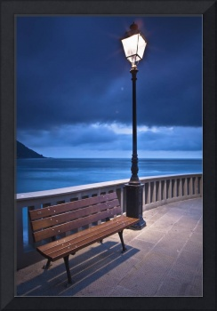 A Bench And Light Post Along The Railing On The Co