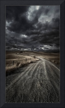 A country road in field with stormy sky above, Tus