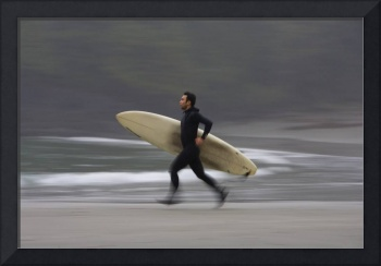 A Surfer Running To The Water With His Board