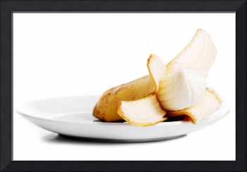 Pilled banana lying in a white bowl. Isolated on w