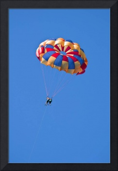 Parasailing under blue sky.