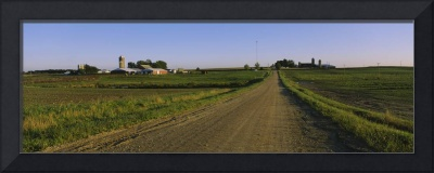 Dirt road passing through fields