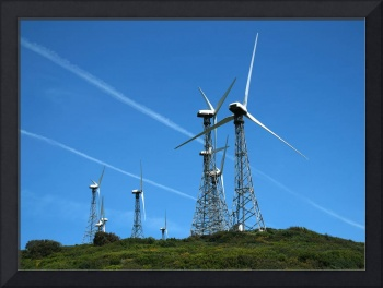 Modern windmills against blue sky with tracks of j