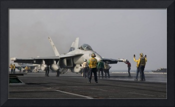 An EA-18G Growler is guided into catapult aboard U