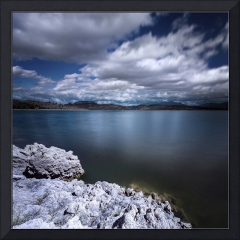 Tranquil lake and rocky shore against cloudy sky,