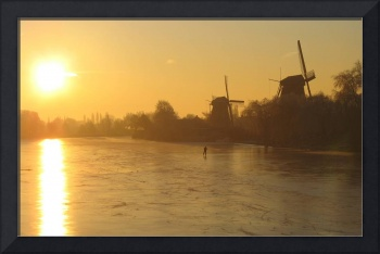 Icy sunrise over river and windmills.