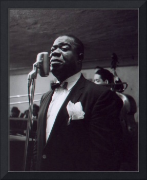 Louis Armstrong stands in front of the microphone