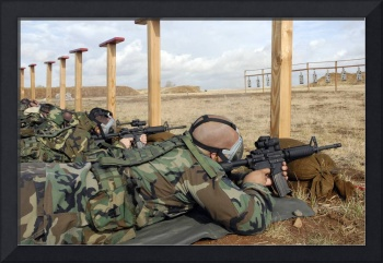 Soldiers sight M4 rifles down range while wearing
