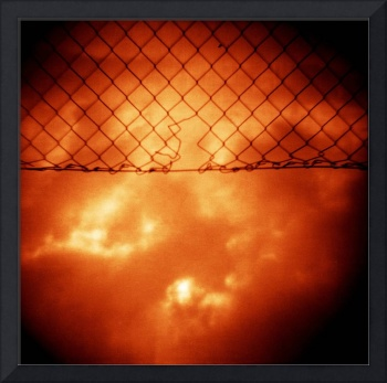 Wire mesh fence against stormy sky